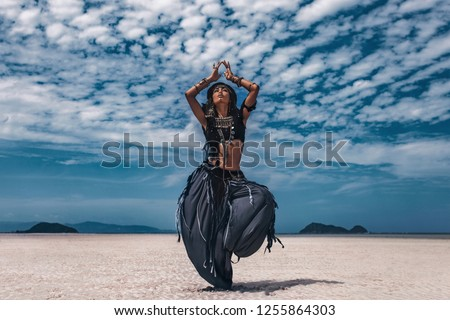 Beautiful young stylish tribal dancer. Woman in oriental costume dancing outdoors Royalty-Free Stock Photo #1255864303