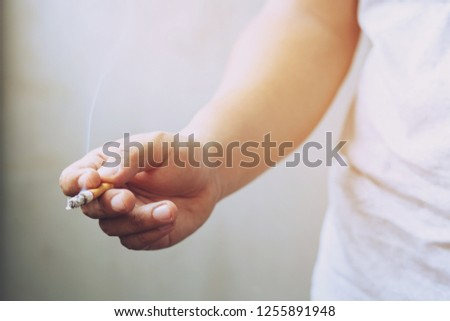 The man smoking a cigarette in hand. Cigarette smoke spread.	 #1255891948