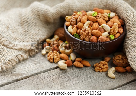 Wooden bowl with nuts on a wooden background, near a bag from burlap. Healthy food and snack, organic vegetarian food. Walnut, pistachios, almonds, hazelnuts and nuts of cashew, walnut. Top view #1255910362