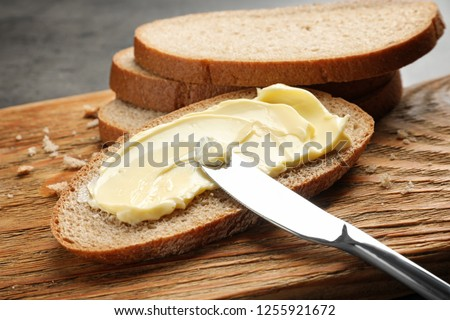 Spreading butter onto toast with knife on wooden board #1255921672