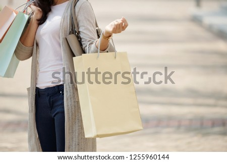 Cropped image of young woman holding many shopping-bags #1255960144
