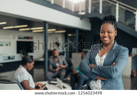 Portrait of a confident black businesswoman with all african american team in the background #1256023498