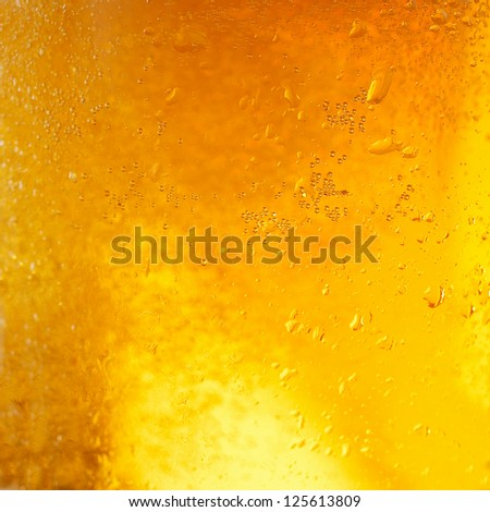 A background created from a closeup of cold light beer in a glass, with condensation droplets on the outside of the glass