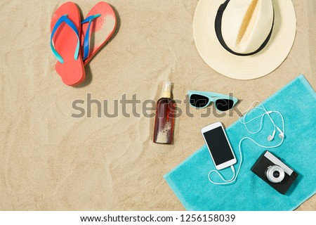 vacation and summer holidays concept - smartphone with earphones and film camera on towel, straw hat, sunglasses, flip flops and bottle of sunscreen oil on beach sand #1256158039