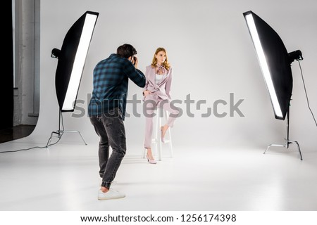 back view of photographer shooting beautiful young female model in photo studio  Royalty-Free Stock Photo #1256174398
