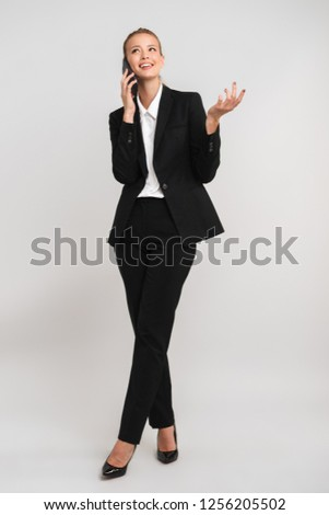 Full length of smiling young business woman isolated over gray background, talking on mobile phone #1256205502