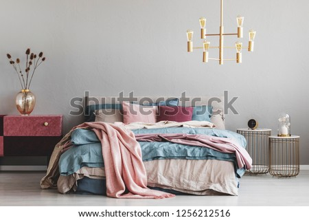 Flowers in stylish glass vase on diy velvet covered pastel pink and burgundy nightstand next to warm bed with blue and beige bedding and pink pillows #1256212516