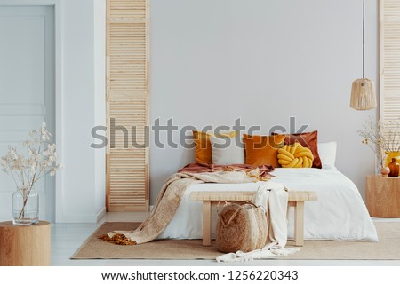 Brown and orange pillows on white bed in natural bedroom interior with wicker lamp and wooden bedside table with vase #1256220343