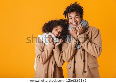 Happy african couple wearing winter clothes standing isolated over yellow background