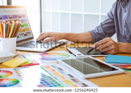 Young creative graphic designer working on project architectural drawing and color swatches, selection coloring on graphic chart with work tools and equipment. #1256240425