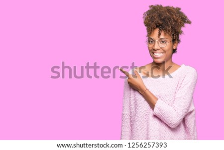 Beautiful young african american woman wearing glasses over isolated background cheerful with a smile of face pointing with hand and finger up to the side with happy and natural expression on face #1256257393