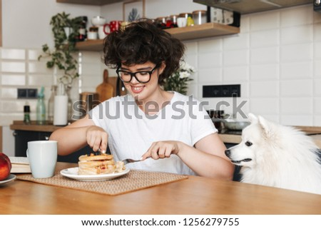 Smiling cheerful girl having tasty breakfast while sitting at the kitchen at home, eating pancakes #1256279755