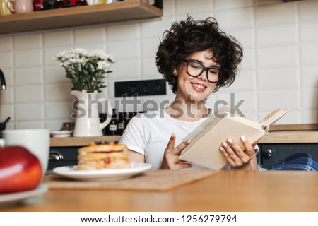 Smiling cheerful girl having tasty breakfast while sitting at the kitchen at home, reading a book #1256279794