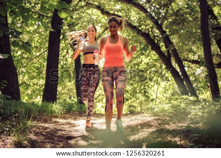 Two young female friends jogging trough the forest.Spring exercise and workout. #1256320261