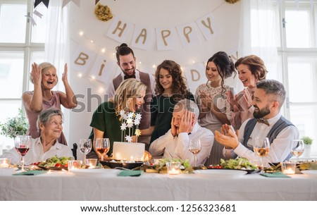 A senior man with multigeneration family celebrating birthday on indoor party. #1256323681