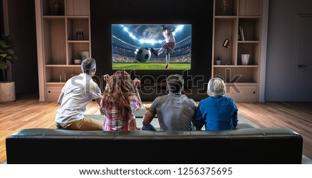 Group of students are watching a soccer moment on the TV and celebrating a goal, sitting on the couch in the living room. The living room is made in 3D. #1256375695