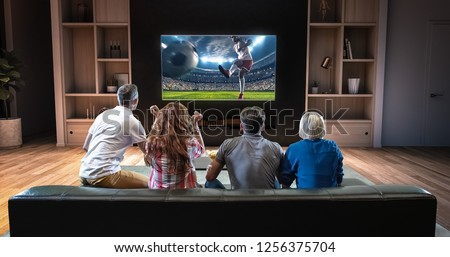 Group of students are watching a soccer moment on the TV and celebrating a goal, sitting on the couch in the living room. The living room is made in 3D. #1256375704