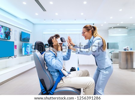 Happy amazed couple trying out virtual reality technology. Man sitting in the chair while woman standing in front of him. Tech store interior. #1256391286