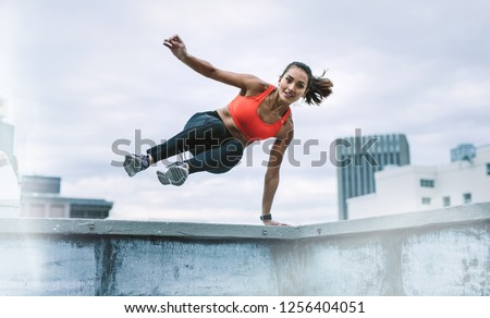 Fitness woman jumping on to the terrace from the rooftop fence with one hand on fence. Woman in fitness wear doing fitness training on rooftop. #1256404051