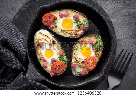Keto diet dish: Avocado boats with ham cubes, quail eggs, cheese and cress sprouts on cast iron skillet with towel on dark background, top view #1256406520