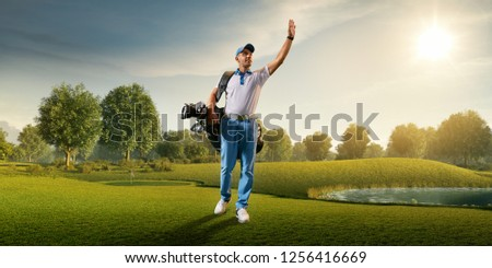 Male golf player on professional golf course. Smiling golfer walking on fairway with golf bag #1256416669
