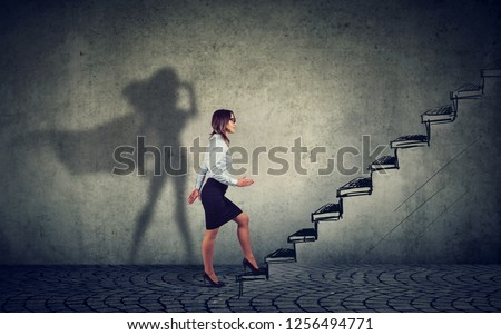 Super hero business woman stepping up on stairs climbing to success on gray wall background #1256494771