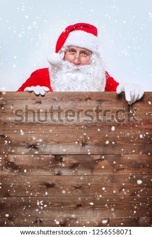 Santa Claus pointing in blank advertisement wooden banner with copy space. Christmas time #1256558071