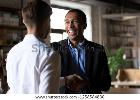 Happy black ceo handshaking rewarding successful worker, smiling african executive manager shaking hand congratulating employee promoting motivating for work achievement, respect recognition concept #1256564830