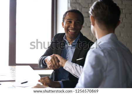 Happy satisfied black client shaking hands thanking manager for good financial deal, african american businessman handshaking partner after successful business negotiations, hiring, buying services #1256570869