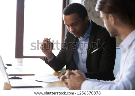 African american businessman reading documents at meeting, black client or customer considering contract terms before signing checking legal paper law conditions preparing to make financial deal #1256570878