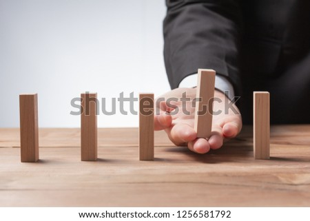 Man hand pick one of many wood block from many wood block in row, risk business concept in choose challenge  idea strategy  different management 