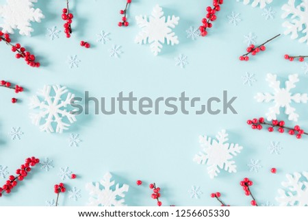 Christmas modern composition. Frame made of green fir tree branches, red berries and snowflakes on pastel blue background. Christmas, New Year, winter concept. Flat lay, top view, copy space #1256605330
