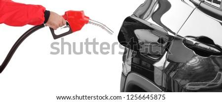 Gasoline pistol pump gun fuel nozzle and car on gas station #1256645875