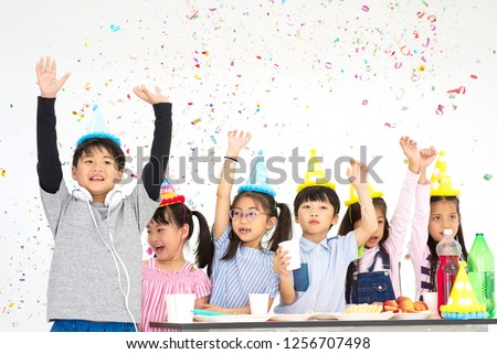 Group of Happy Asian Kids Raise Hands Up and Enjoy Throwing Colorful Confetti with Friends in Celebrate Event Cute Children Having Fun with Friends at School in Christmas New Year Party #1256707498