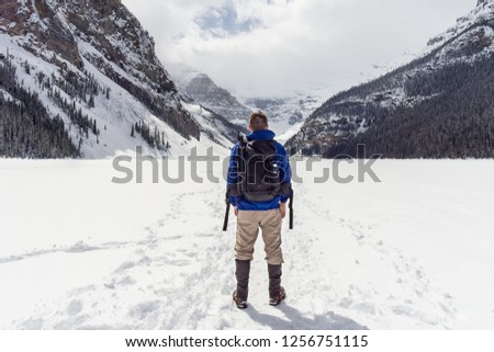 Hiker Standing on Frozen Alpine Lake #1256751115