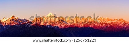 Panoramic view during sunset over snow cladded Panchchuli peaks falls in great Himalayan mountain range from small hamlet Munsiyari, Kumaon region, Uttarakhand, India. #1256751223