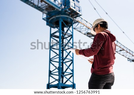 Engineer hand holding and looking blueprint plan on construction site with blue sky background.Architect inspects construction work and out of focus tower crane background. #1256763991