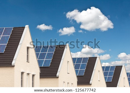 Row of Dutch new houses with solar panels attached on the roofs #125677742