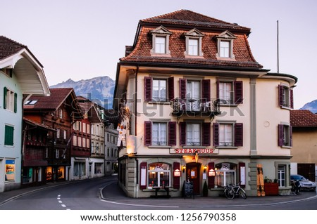 SEP 25, 2013 Interlaken, Switzerland - Evening street scene with car and old vintage Swiss style buildings of Unterseen town and old town area of Interlaken, Switzerland #1256790358