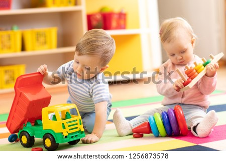 Kids playing with educational toys. Children sit on a rug in a play room at home or kindergarten. Toddler boy with toy lorry and baby girl with rings. #1256873578