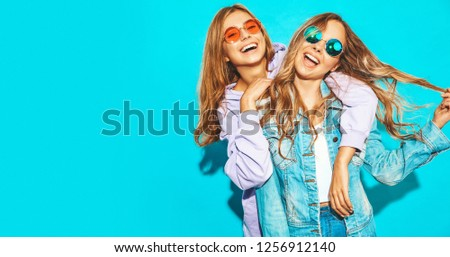 Two young beautiful blond smiling hipster girls in trendy summer clothes. Sexy carefree women posing near blue wall in sunglasses. Positive models #1256912140