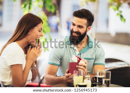 Man surprises woman with a gift in cafe #1256945173
