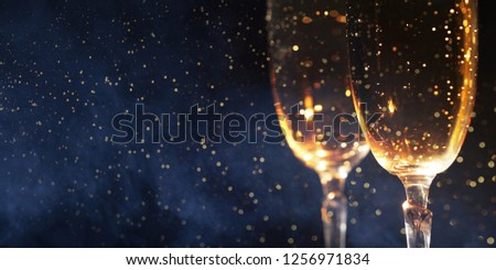 Christmas decoration with two glasses of champagne and lights on a wooden background, Happy New Year. Celebration. Selective focus and small depth of field. #1256971834