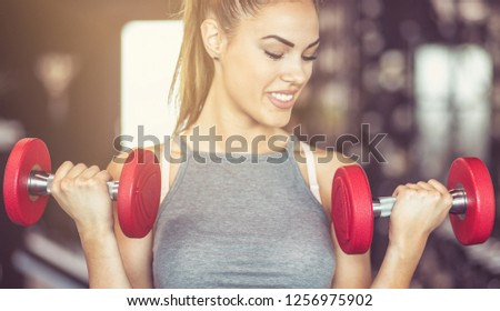 I am strong woman. Sportswoman working exercise for hands with weight. Close up. #1256975902