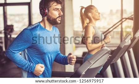 Music and exercises go together. Couple working exercise on treadmill. Focus is on man.  #1256975917