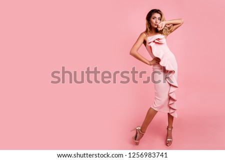 Full height fashion  image of blonde woman with perfect wavy hairstyle in pink  party dress posing on pastel pink background. Hight heels. Surprise face.   Space fo text.  #1256983741