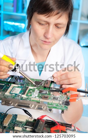Tech tests electronic equipment in service centre #125703095
