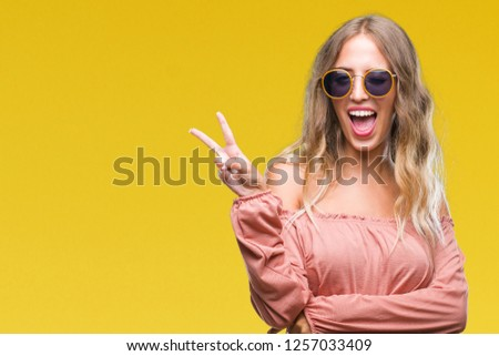 Beautiful young blonde woman wearing retro sunglasses over isolated background smiling with happy face winking at the camera doing victory sign. Number two. #1257033409