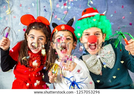 Three kids celebrating Carnival  together at home Royalty-Free Stock Photo #1257053296