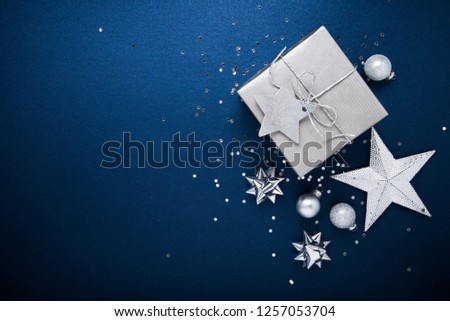 Merry Christmas and Happy Holidays greeting card, frame, banner. New Year. Noel. Silver Christmas gifts, ornaments on blue background top view. Winter holiday xmas theme. Flat lay. #1257053704